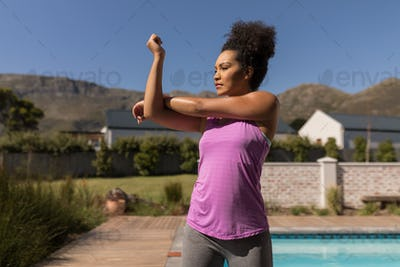 Woman performing stretching exercise next to the swimming pool in the backyard of home