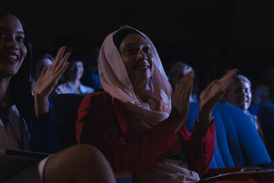 Low angle view of mixed race businesswoman sitting  and clapping in the auditorium