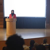 Front view of mixed race businesswoman giving speech in front of audience in the auditorium