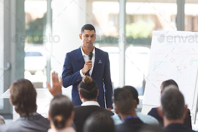 Businessman speaking in front of diverse group of people with microphone at conference