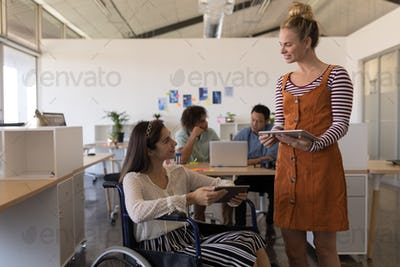 Pretty disabled female executive interacting with her casually dressed coworker in office