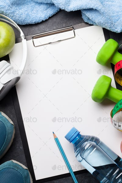Fitness concept. Dumbbells, sneakers, headphones and apple