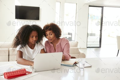 Middle aged black woman helping her teenage daughter with homework, front view