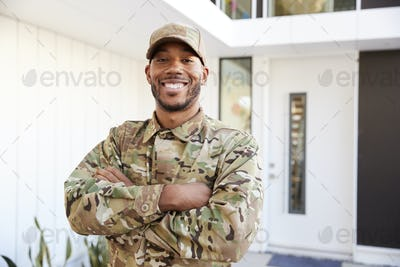 Soldier in camouflage standing outside modern house with arms crossed smiling to camera, close up