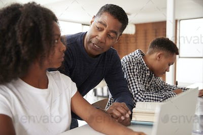 Middle aged black dad helping his teen kids with homework, low angle, close up
