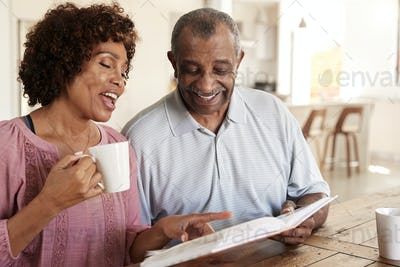 Senior black man and his middle aged daughter looking through photo album together at home, close up