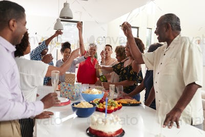 Millennial black woman pouring champagne during a three generation family celebration at home