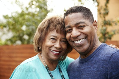 Senior black woman and her middle aged son smiling to camera, head and shoulders, close up