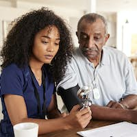Female healthcare worker checking the blood pressure of a senior man during a home visit
