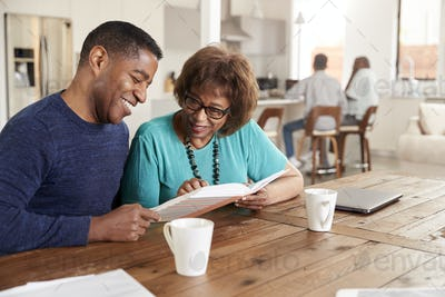 Middle aged black man looking through a photo album with his mother at home, close up