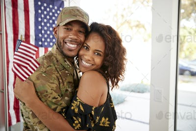 Millennial black soldier and his wife embracing at home and smiling to camera,close up