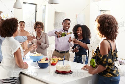 Three generation black family raising glasses to make a toast during a celebration at home