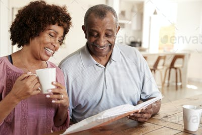 Middle aged black woman and her dad looking through photo album together at home, close up