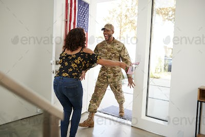 Millennial black male soldier returning home into the arms open of his wife, close up