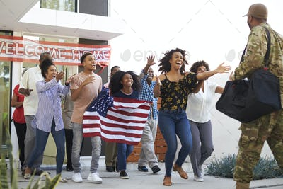 Three generation black family running out of house to welcome soldier returning home, low angle view
