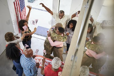 Young black male soldier welcomed home by three generation family, elevated view
