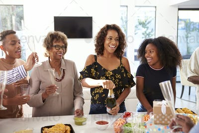 Millennial black woman opening champagne to celebrate with her family,front view