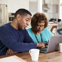 Middle aged black man helping his mother use a laptop computer at home, close up