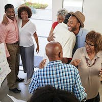 Black family members embracing at a surprise party, elevated view
