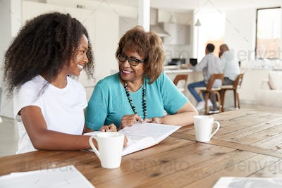 Teenage black girl and her grandmother looking through a photo album smiling at each other, close up