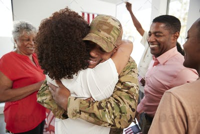 Millennial black soldier returning home embracing family members,close up