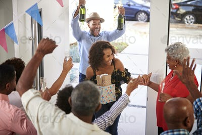 Three generation family throwing a surprise party welcoming guests at the front door,elevated view