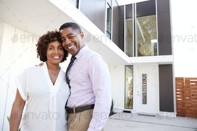 Middle aged black couple stand outside admiring their modern home, back view