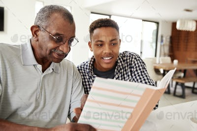 Young black man looking at a photo album at home with his grandfather, close up
