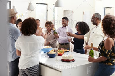 Middle aged black man pouring champagne to celebrate at home with his three generation family