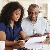 Female healthcare worker checking test results with a senior man during a home health visit