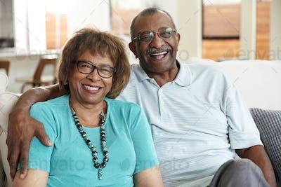 Senior black couple sitting at home, smiling to camera, close up