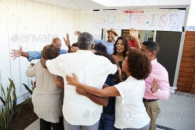 Three generation black family welcoming grandparents to a surprise party