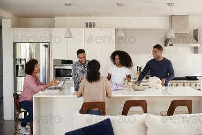Black family in their kitchen talking and preparing a family meal together