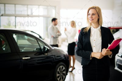 Portrait of young saleswoman in car dealership