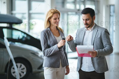 Professional salesperson selling cars at dealership to buyer