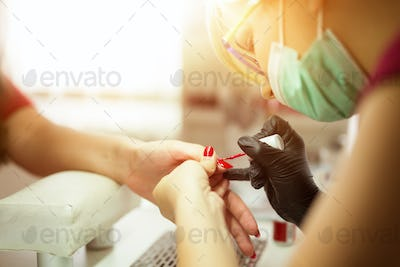 Manicurist working on client nails
