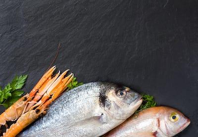 Fresh fish and seafood on dark vintage board
