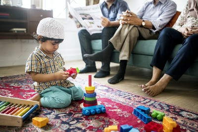Muslim family relaxing and playing at home