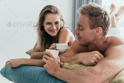 couple lying on bed and having a cup of coffee