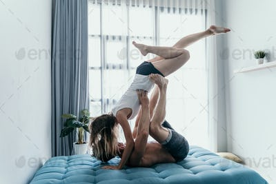 couple carrying and kissing beautiful girl upside down