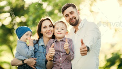 Positive and stylish family gesturing super by fingers at camera