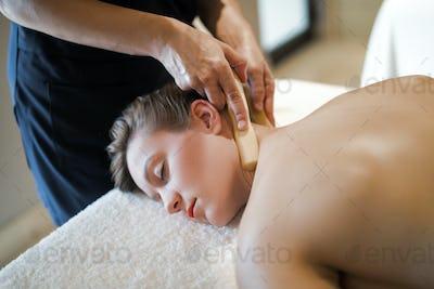 Masseur massaging masseuse at wellness resort