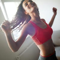 Fit sportswoman exercising at home