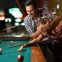 Couple playing billiards together