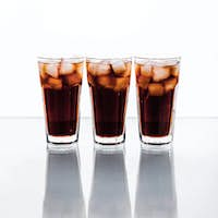 three glasses of cola and ice on a white background. soft drinks