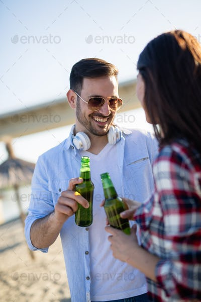 Happy couple having fun and drinking at beach