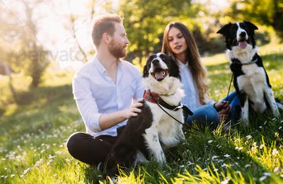 Beautiful couple walking dogs and bonding in nature