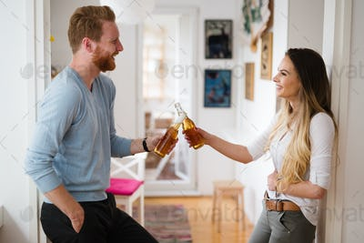 Happy couple drinking beer and toasting at home