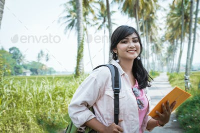 happy smiling female student outdoor with bag and book