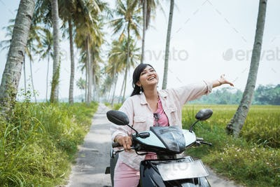 woman riding her scooter bike in tropical country road